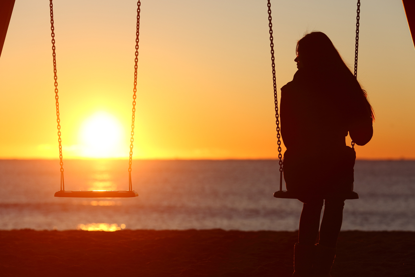 Single woman alone swinging on the beach and looking the other seat