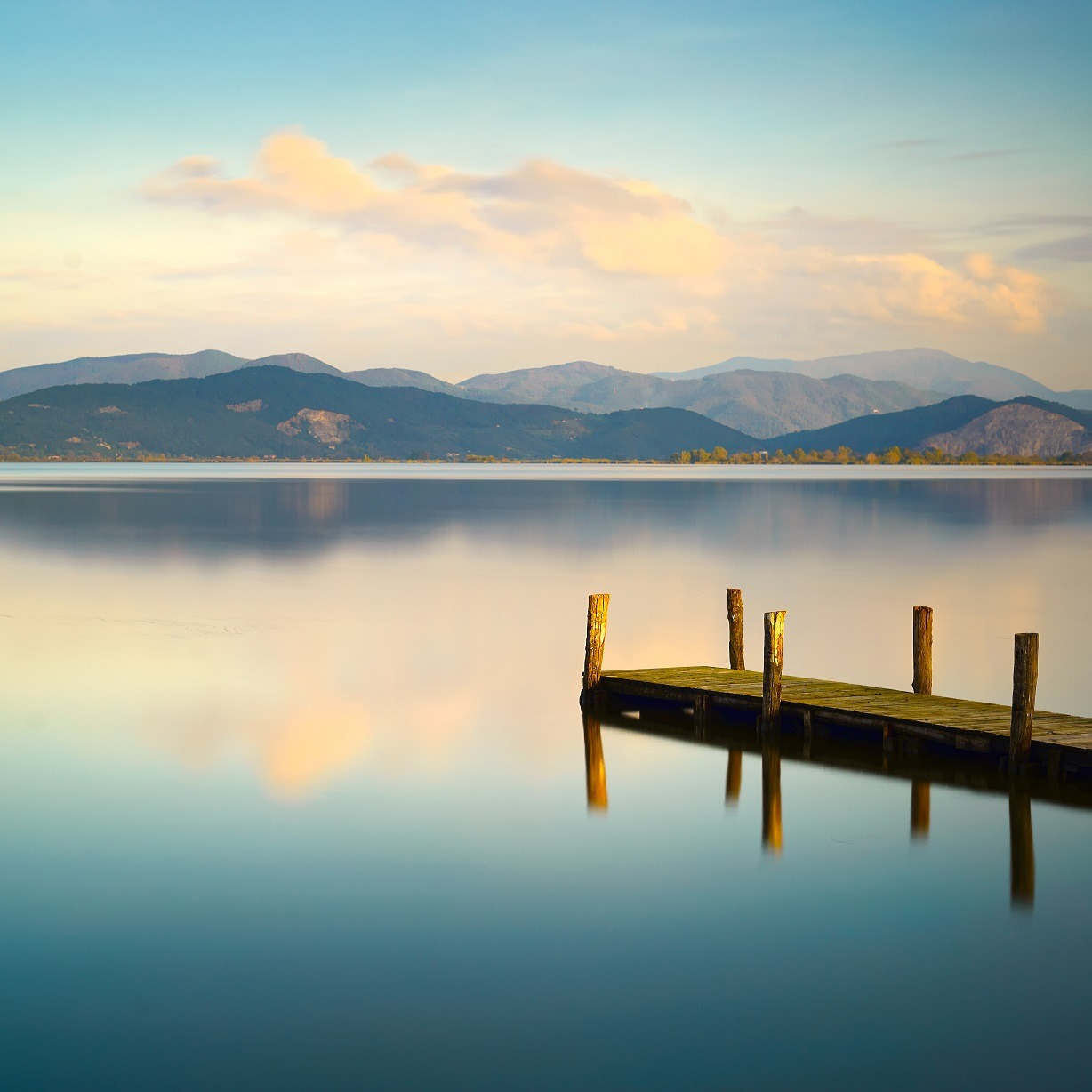 Wooden pier or jetty and on a blue lake sunset and cloudy sky reflection on water.