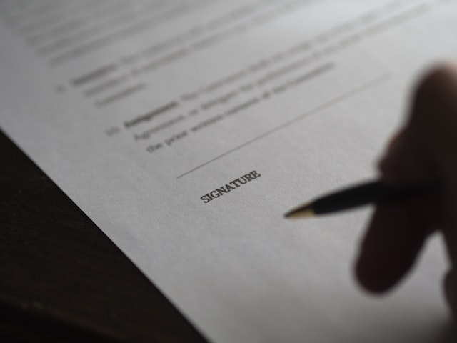 closeup hand and pen at signature line of a contract; highlighting the settlement process in motor vehicle accidents