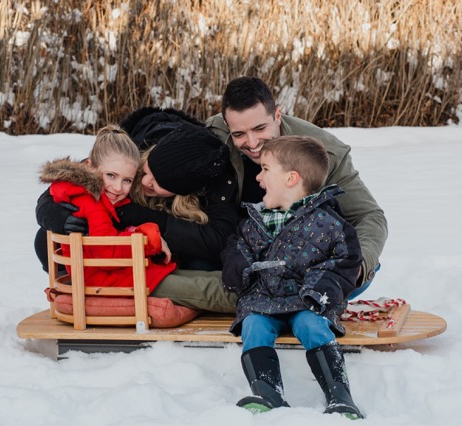 Family in Winter with Sled and jackets and snow boots